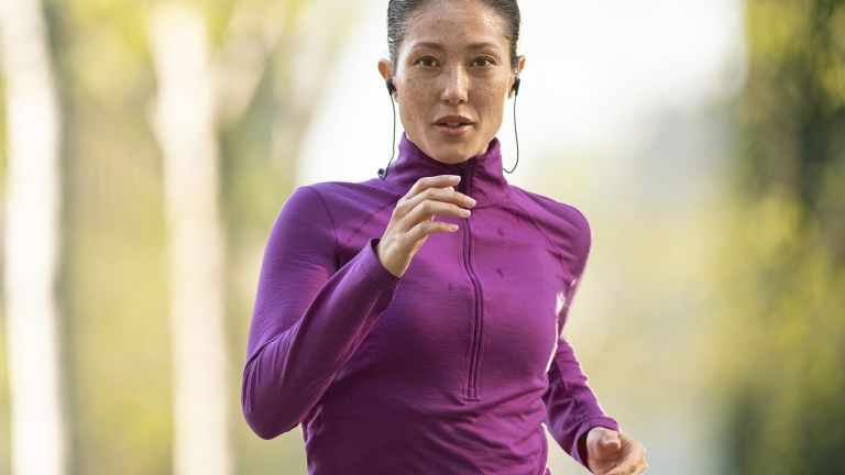 Woman listening to fitness audio apps as she runs