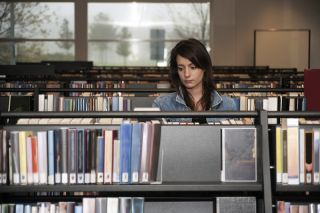 An introverted young woman in the library.