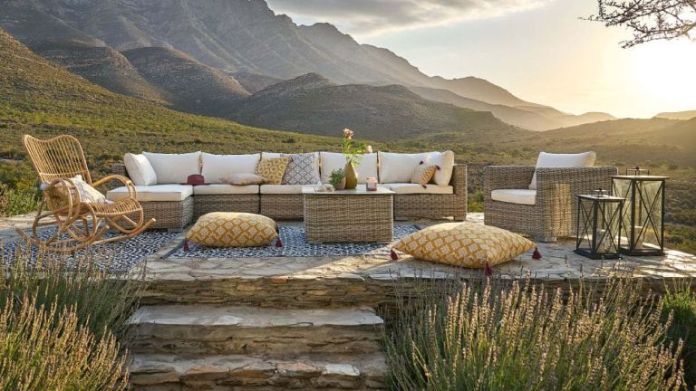 A rattan outdoor rocking chair on an outdoor patio area with a sectional sofa and a vista of mountains behind
