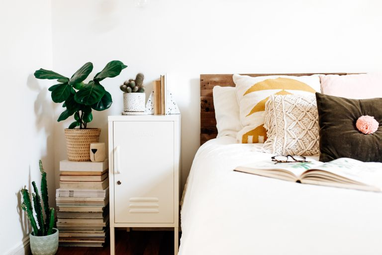 Uni room ideas: All white bedroom with houseplants and boho style cushions