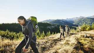 Three woman hike up a trail with the mountains in the background