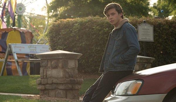 Love Simon Nick Robinson sitting on his car's hood at the fair