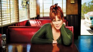 A press shot of Beth Hart sat at a table, taken in 2016
