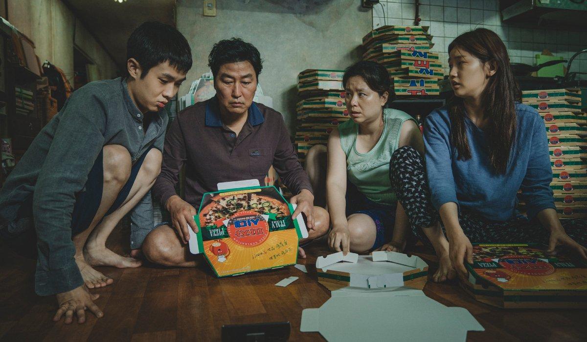 Parasite the Kim family folding pizza boxes in their apartment