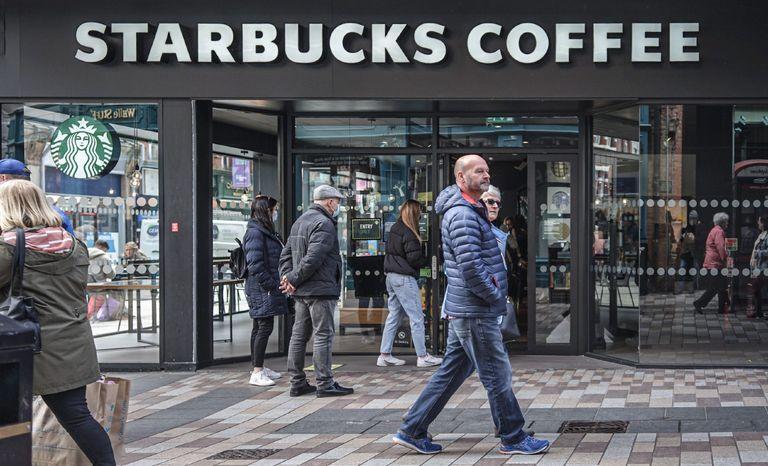 Customers queue to enter Starbucks Coffee Shop.