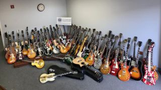A lineup shot of 85 counterfeit Fenders, Gibsons and other electric guitars