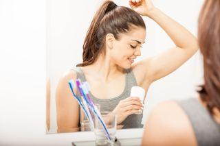 A woman puts on deodorant.