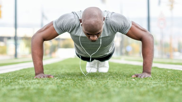 Man learning how to do a push up outdoors