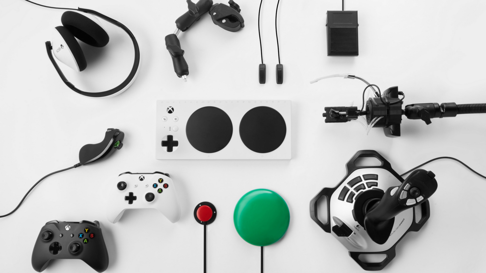 Microsoft adaptive controller surrounded by Microsoft peripherals