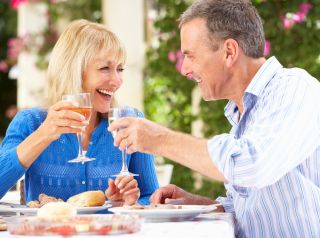 An older couple toasts with glasses with wine.