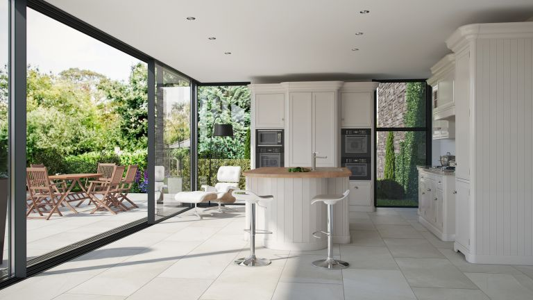 kitchen with large sliding doors leading out to a terrace with porcelain floor tiles