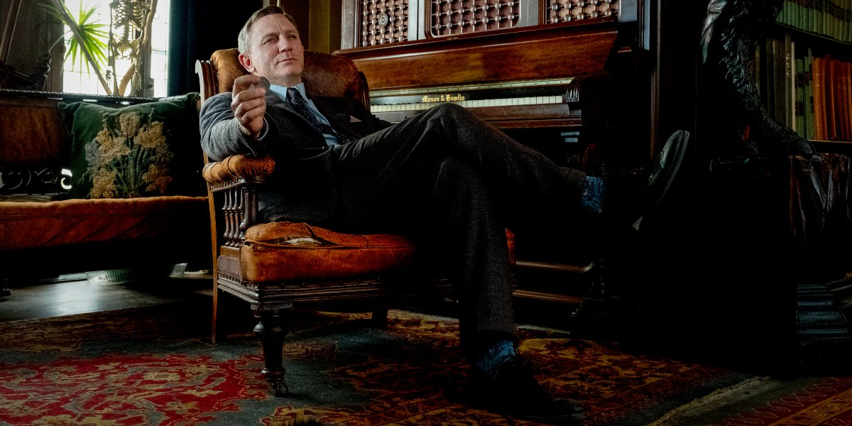 Daniel Craig sits back with a bemused smile in the library in Knives Out.