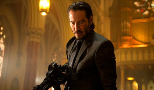John Wick with bloody face and gun
