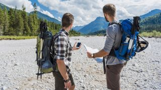 best navigational apps: hikers with map and smartphone