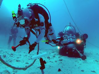 NASA astronaut Dottie Metcalf-Lindenburger tests different ways to anchor to the surface of an asteroid on a simulated spacewalk on the ocean floor during the NEEMO 16 mission.