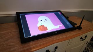 The Huion Kamvas 24 Pro 4K on a sideboard displaying a spooky Halloween ghost