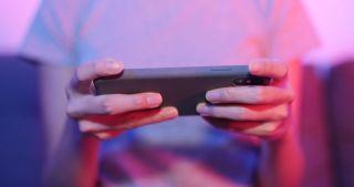 Eine Person hält ein Smartphone vertikal in der Hand, um darauf zu zocken.