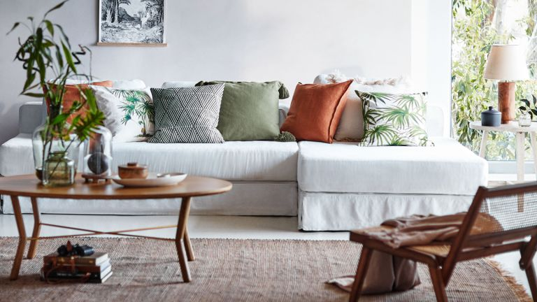 Living room with tropical print cushions and a white sofa by H&M Home