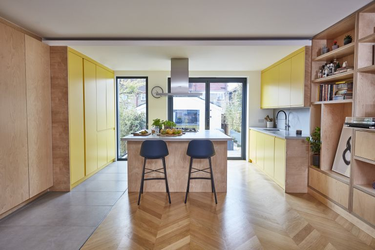 Plywood kitchen with yellow units and an island with dark blue and black bar stools