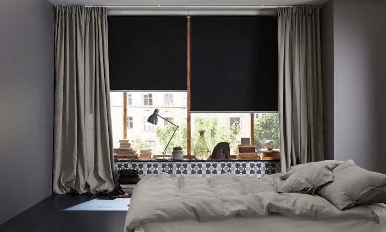 Blackout blinds with gray drapes in bedroom with houseplants and dark bedding