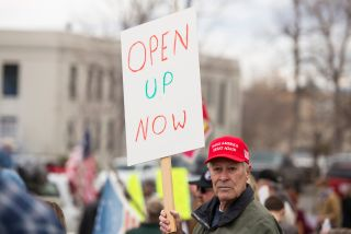 On April 19, a protestor in Helena, Montana holds up a sign to protest stay-at-home measures. Similar protests have taken hold across the country over the past couple of weeks.