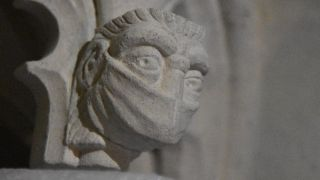 A carved face wearing a mask commemorates the restoration project taking place during the COVID-19 pandemic.