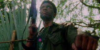 Da 5 Bloods Chadwick Boseman walking armed through the jungle