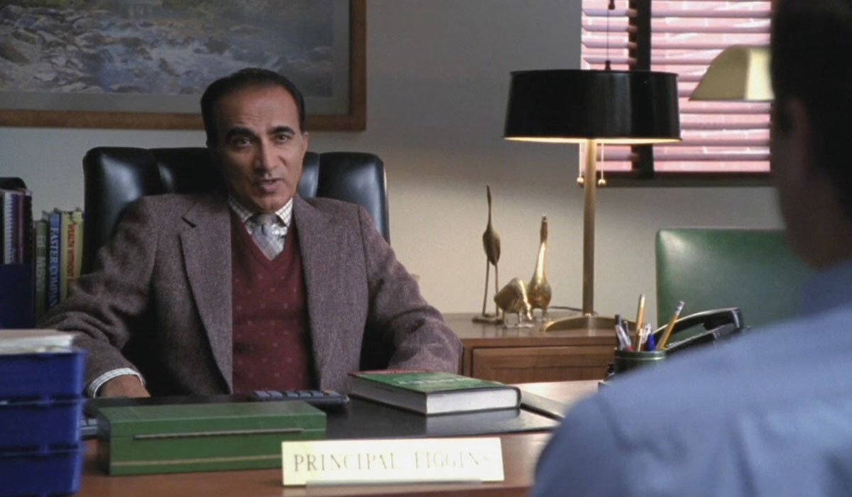Iqbal Theba sitting at a desk talking to a student in Glee.