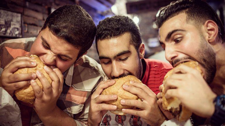 Men eating large burgers