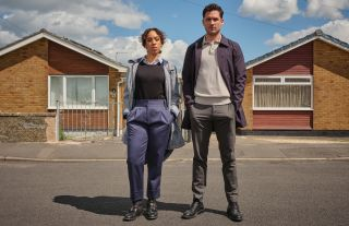 Pearl Mackie as DS Jen Rafferty and Ben Aldridge as DI Matthew Venn in The Long Call, both standing with their hands in their pockets on the street in front of a row of bungalows