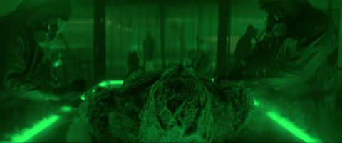 Swamp Thing lays on a dissection table surrounded by masked men