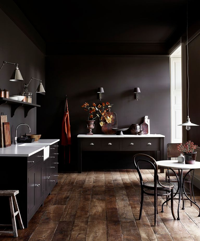 Dark painted kitchen ideas with dark aubergine walls and cabinetry, a wooden floor and bistro dining table, with white, wood and burnt orange accents.