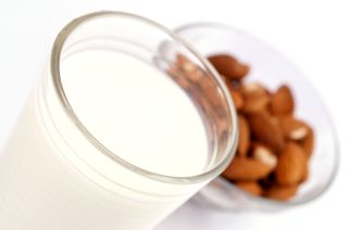 A glass of milk and a bowl of almonds