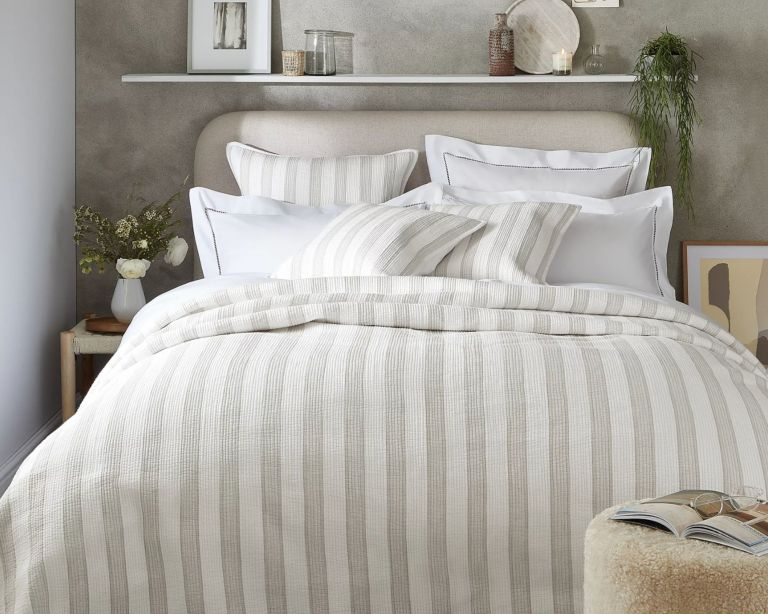 The White Company Fareham Quilt in grey and white stripes on bed with matching cushions