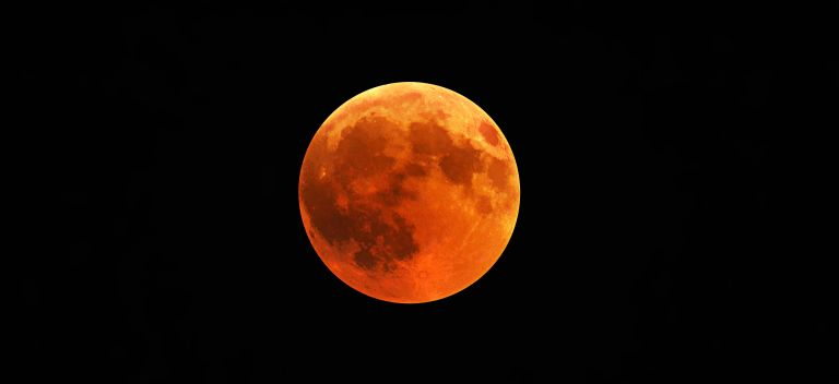 Black sky with a orange red Blood Moon in the centre