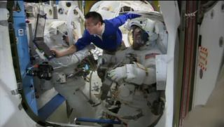 NASA astronauts Rick Mastracchio and Steve Swanson don their spacesuits with the help of Japanese astronaut Koichi Wakata (in blue) on April 23, 2014 ahead of a 2.5-hour spacewalk to replace a dead computer on the International Space Station.