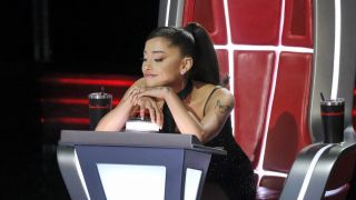 Ariana Grande leaning on her button on The Voice