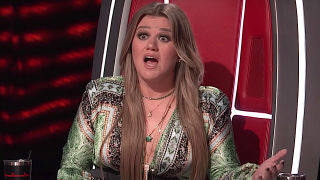 Screenshot of Kelly Clarkson looking shocked on The Voice