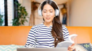 Woman looking at laptop, wearing headphones and holding book.