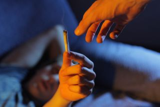 A man hands a marijuana cigarette to someone