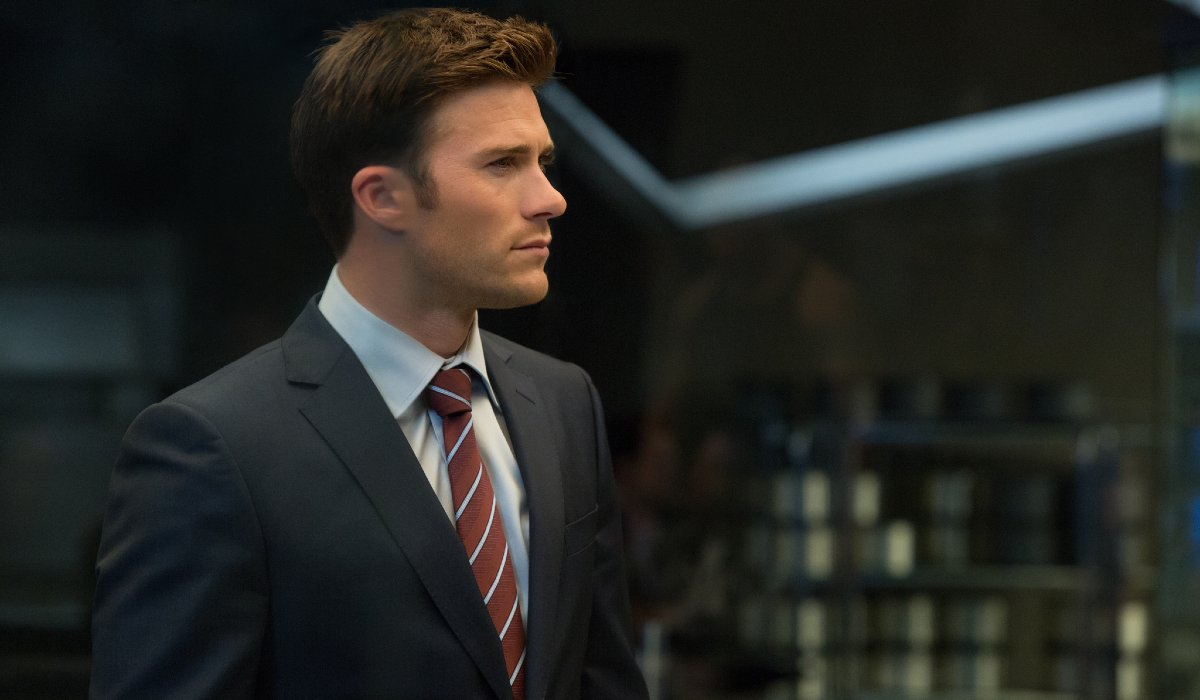 Scott Eastwood standing attentively in a suit in The Fate of the Furious.