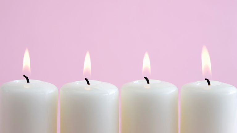 white candles burning on pink background