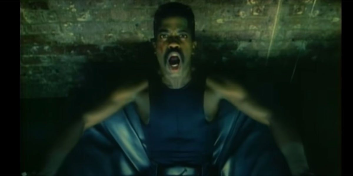 Cameo singing into the camera with a mustache and black tanktop.