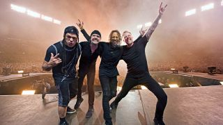 A photograph of Metallica on stage posing and throwing the horns