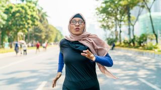 A woman wearing a blue sports top and pink hijab runs in a marathon