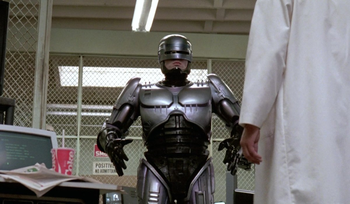 Robocop walking towards a scientist in the garage