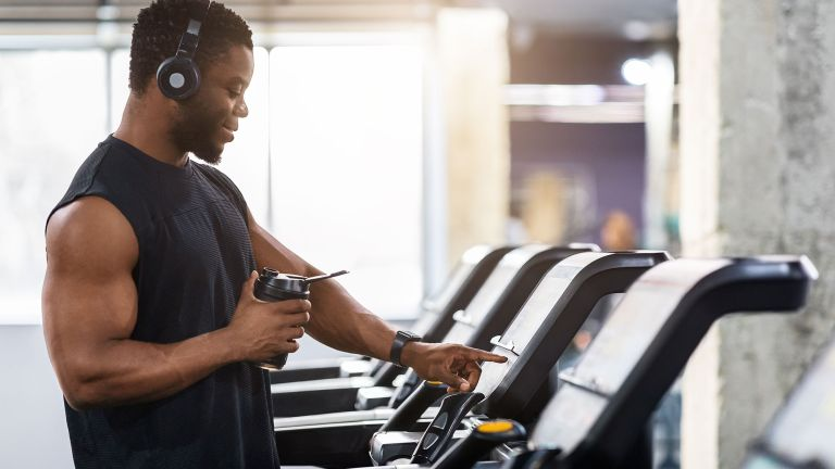 A man in the gym figuring out how to use a treadmill