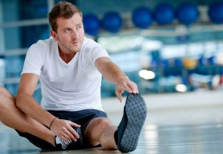 Man at the gym doing stretching exercises and smiling on the floor