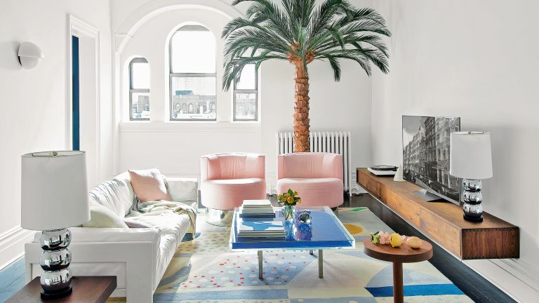 Small living room with pink chairs and floating TV unit