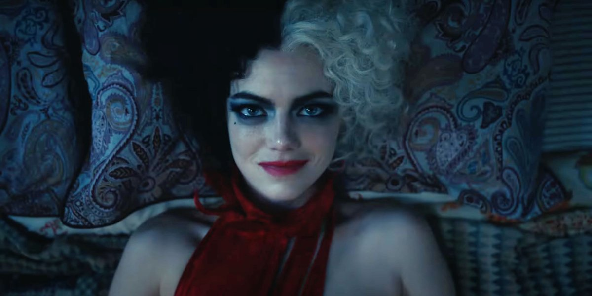 Emma Stone smiles while lying in bed in Cruella.